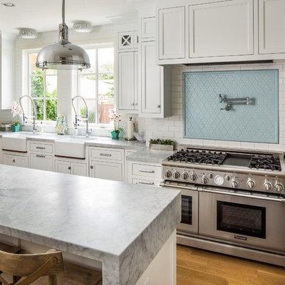 Kitchen - transitional u-shaped kitchen idea in Salt Lake City with a farmhouse sink, shaker cabinets, white cabinets, blue backsplash, subway tile backsplash and stainless steel appliances