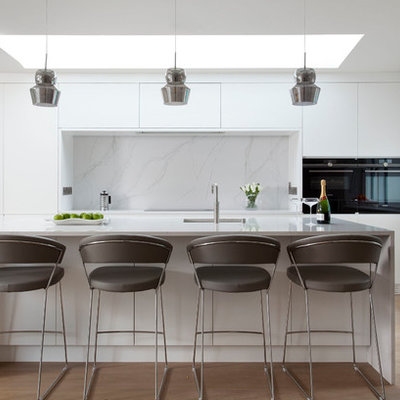 Example of a mid-sized trendy galley light wood floor and beige floor kitchen design in Dublin with flat-panel cabinets, white backsplash, marble backsplash, black appliances, an island, an undermount sink and marble countertops