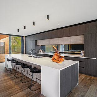 Design ideas for an expansive contemporary galley open plan kitchen in Central Coast with flat-panel cabinets, dark wood cabinets, solid surface benchtops, black splashback, mirror splashback, black appliances, with island and white benchtop.