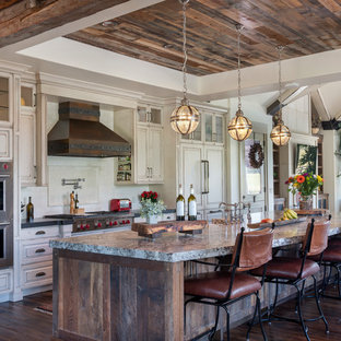 Country galley kitchen in Denver with raised-panel cabinets, distressed cabinets, white splashback, stainless steel appliances, dark hardwood floors, with island, brown floor and grey benchtop.