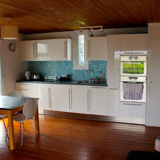 Design ideas for a small beach style single-wall eat-in kitchen in Sussex with a single-bowl sink, flat-panel cabinets, white cabinets, laminate benchtops, blue splashback, glass tile splashback, stainless steel appliances, medium hardwood floors and no island.