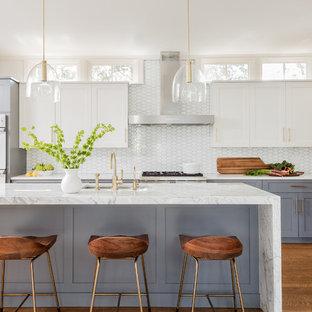 ボストンの中くらいのトランジショナルスタイルのおしゃれなキッチン (アンダーカウンターシンク、大理石カウンター、白いキッチンパネル、ガラスタイルのキッチンパネル、シルバーの調理設備、無垢フローリング、シェーカースタイル扉のキャビネット、白いキャビネット、茶色い床) の写真