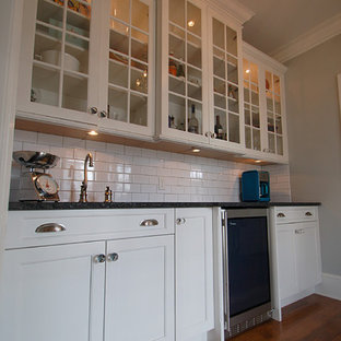 Traditional eat-in kitchen photos - Inspiration for a timeless l-shaped medium tone wood floor eat-in kitchen remodel in New York with an undermount sink, recessed-panel cabinets, white cabinets, quartz countertops, gray backsplash, subway tile backsplash, stainless steel appliances and an island