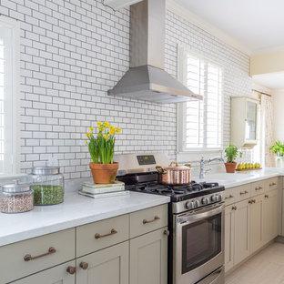 ジャクソンビルのシャビーシック調のおしゃれなキッチン (シェーカースタイル扉のキャビネット、グレーのキャビネット、白いキッチンパネル、サブウェイタイルのキッチンパネル、シルバーの調理設備の、ベージュの床、白いキッチンカウンター、一体型シンク) の写真