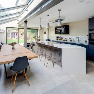 Medium sized contemporary single-wall kitchen in London with a submerged sink, flat-panel cabinets, blue cabinets, stainless steel appliances, slate flooring, an island and grey floors.