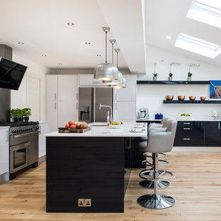 This is an example of a large contemporary l-shaped open plan kitchen in West Midlands with white cabinets, stainless steel appliances, light hardwood flooring, beige floors, white worktops, a submerged sink, flat-panel cabinets, grey splashback and an island.