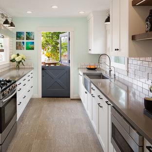 サンディエゴの中くらいのビーチスタイルのおしゃれなキッチン (エプロンフロントシンク、シェーカースタイル扉のキャビネット、白いキャビネット、クオーツストーンカウンター、白いキッチンパネル、サブウェイタイルのキッチンパネル、シルバーの調理設備、磁器タイルの床、アイランドなし、グレーの床、紫のキッチンカウンター) の写真