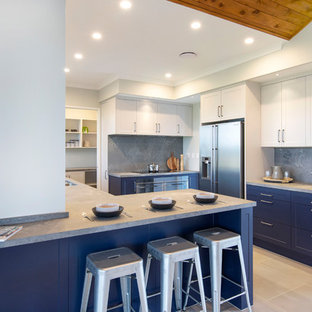 This is an example of a mid-sized country u-shaped separate kitchen in Hamilton with a double-bowl sink, shaker cabinets, blue cabinets, concrete benchtops, grey splashback, stainless steel appliances, ceramic floors, a peninsula, grey floor and grey benchtop.