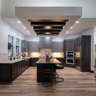 Design ideas for an expansive contemporary u-shaped enclosed kitchen in Other with a submerged sink, flat-panel cabinets, grey cabinets, marble worktops, beige splashback, ceramic splashback, stainless steel appliances, medium hardwood flooring, multiple islands, brown floors and yellow worktops.