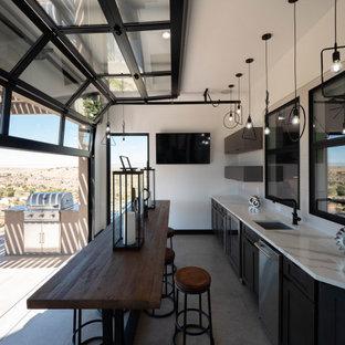 Пример оригинального дизайна: огромная отдельная, п-образная кухня в современном стиле с врезной раковиной, плоскими фасадами, серыми фасадами, мраморной столешницей, бежевым фартуком, фартуком из керамической плитки, техникой из нержавеющей стали, паркетным полом среднего тона, двумя и более островами, коричневым полом и желтой столешницей