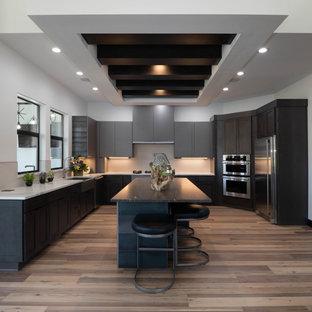 Inspiration för ett avskilt, mycket stort funkis gul gult u-kök, med en undermonterad diskho, släta luckor, grå skåp, marmorbänkskiva, beige stänkskydd, stänkskydd i keramik, rostfria vitvaror, mellanmörkt trägolv, flera köksöar och brunt golv