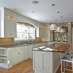 This is an example of a country u-shaped kitchen in Boston with shaker cabinets, wood benchtops, beige splashback, grey cabinets, stainless steel appliances and glass tile splashback.