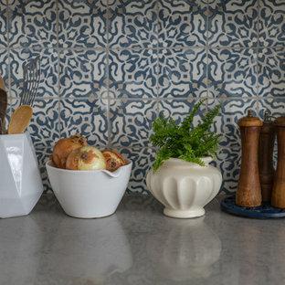 Bild på ett avskilt funkis u-kök, med en rustik diskho, skåp i shakerstil, vita skåp, rostfria vitvaror, en köksö, grått golv, bänkskiva i kvarts, flerfärgad stänkskydd och stänkskydd i keramik