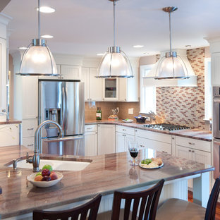 Inspiration for a large traditional u-shaped eat-in kitchen in Providence with subway tile splashback, granite benchtops, beige splashback, an undermount sink, shaker cabinets, white cabinets, stainless steel appliances, a peninsula and medium hardwood floors.