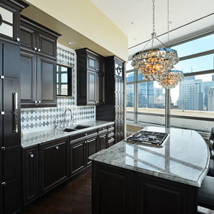 Elegant single-wall eat-in kitchen photo in Chicago with a drop-in sink, raised-panel cabinets, dark wood cabinets, marble countertops, white backsplash and stainless steel appliances