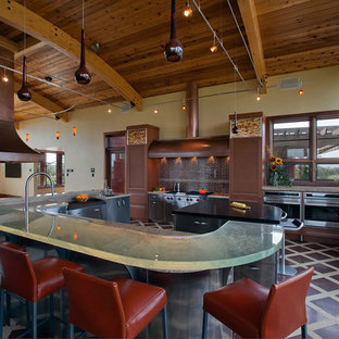 This is an example of a large contemporary u-shaped eat-in kitchen in Boston with stainless steel appliances, an undermount sink, glass benchtops, multiple islands, stainless steel cabinets, recessed-panel cabinets, brown splashback, glass tile splashback, marble floors and multi-coloured floor.