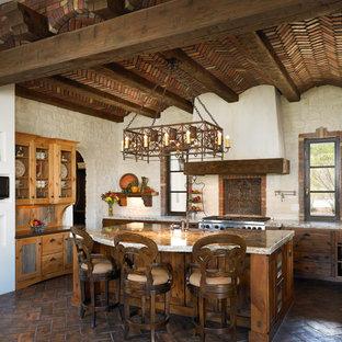 Idee per una cucina a L mediterranea con ante con finitura invecchiata e elettrodomestici in acciaio inossidabile