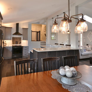 Large transitional eat-in kitchen in Philadelphia with an undermount sink, recessed-panel cabinets, grey cabinets, granite benchtops, white splashback, subway tile splashback, stainless steel appliances, vinyl floors, with island, brown floor and white benchtop.