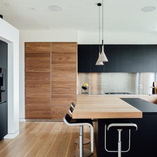 Ejemplo de cocina en L, moderna, con armarios con paneles lisos, puertas de armario negras, encimera de acero inoxidable, salpicadero metalizado, electrodomésticos con paneles, suelo de madera clara, una isla y suelo beige