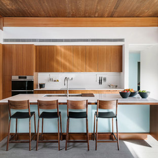 Contemporary open concept kitchen appliance - Example of a trendy open concept kitchen design in Other with medium tone wood cabinets, solid surface countertops, white backsplash, an island and white countertops