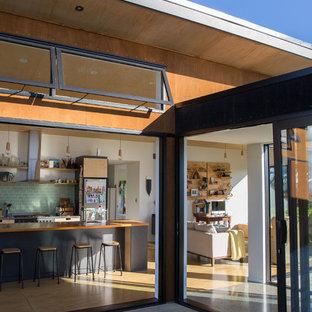 Esempio di una cucina nordica con lavello a doppia vasca, ante lisce, ante in legno chiaro, top in legno, paraspruzzi verde, paraspruzzi con piastrelle di vetro, elettrodomestici in acciaio inossidabile, pavimento in compensato, un'isola e pavimento marrone