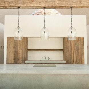 Diseño de cocina de galera, rústica, con fregadero integrado, puertas de armario de madera oscura, encimera de cemento y una isla