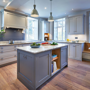 This is an example of a large traditional kitchen/diner in Buckinghamshire with an integrated sink, shaker cabinets, granite worktops, grey splashback, black appliances, an island and white worktops.