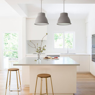 Photo of a contemporary l-shaped kitchen in Sydney with a double-bowl sink, flat-panel cabinets, white cabinets, stainless steel appliances, light hardwood floors, with island and beige floor.