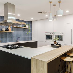 Contemporary u-shaped kitchen in Perth with an undermount sink, flat-panel cabinets, white cabinets, wood benchtops, blue splashback, panelled appliances, medium hardwood floors, a peninsula, brown floor and white benchtop.