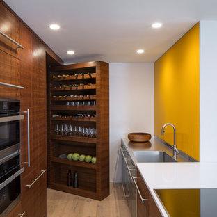 Inspiration pour une cuisine parallèle minimaliste avec un évier intégré, un placard à porte plane, des portes de placard en bois brun, un plan de travail en inox, une crédence jaune, une crédence en feuille de verre, un électroménager en acier inoxydable, un sol en bois clair, une péninsule, un sol beige et un plan de travail gris.