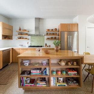 Retro Wohnküche in L-Form mit Doppelwaschbecken, flächenbündigen Schrankfronten, hellbraunen Holzschränken, Arbeitsplatte aus Holz, Küchenrückwand in Grün, Küchengeräten aus Edelstahl, Kücheninsel und braunem Boden in Sonstige