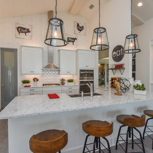 Country u-shaped kitchen in Milwaukee with a farmhouse sink, shaker cabinets, white cabinets, white splashback, subway tile splashback, stainless steel appliances, dark hardwood floors, a peninsula and grey floor.