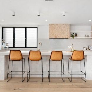 Inspiration for a beach style l-shaped kitchen in Sydney with flat-panel cabinets, medium wood cabinets, white splashback, panelled appliances, light hardwood floors, with island, beige floor and white benchtop.