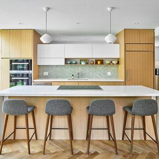 Foto på ett funkis vit kök, med en undermonterad diskho, släta luckor, vita skåp, grönt stänkskydd, integrerade vitvaror, ljust trägolv och en köksö
