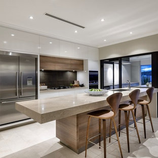 Mid-sized contemporary open concept kitchen designs - Example of a mid-sized trendy galley limestone floor open concept kitchen design in Perth with an undermount sink, white cabinets, marble countertops, gray backsplash, glass sheet backsplash, white appliances and an island