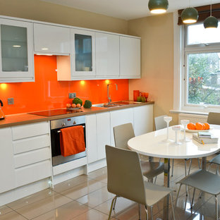 Design ideas for a mid-sized contemporary l-shaped eat-in kitchen in London with flat-panel cabinets, white cabinets, wood benchtops, orange splashback, glass sheet splashback, stainless steel appliances, porcelain floors and no island.