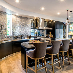 This is an example of a contemporary kitchen in Adelaide with flat-panel cabinets, black cabinets, stainless steel benchtops, stainless steel appliances, with island, an integrated sink, metallic splashback, metal splashback, light hardwood floors and beige floor.