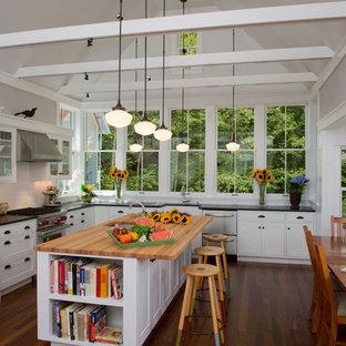 Foto di una cucina country con lavello sottopiano, ante in stile shaker, ante bianche, top in legno, paraspruzzi bianco e elettrodomestici in acciaio inossidabile