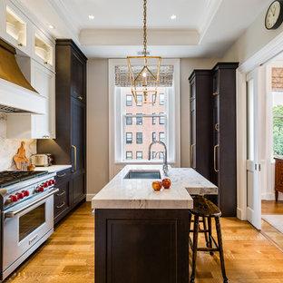 Idee per una piccola cucina parallela chic con lavello sottopiano, ante con riquadro incassato, paraspruzzi bianco, elettrodomestici da incasso, pavimento in legno massello medio, isola, pavimento arancione, top bianco e ante nere