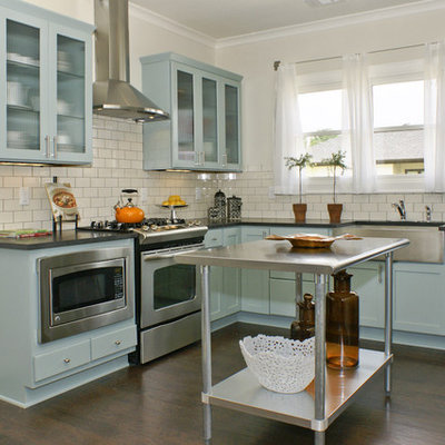 Example of a mid-sized cottage l-shaped dark wood floor eat-in kitchen design in Birmingham with stainless steel appliances, a farmhouse sink, shaker cabinets, blue cabinets, solid surface countertops, white backsplash, subway tile backsplash and an island