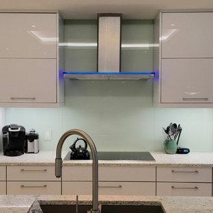 Immagine di una grande cucina contemporanea con ante a persiana, ante bianche, paraspruzzi verde e paraspruzzi con lastra di vetro