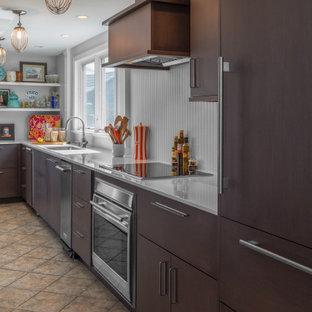 Geschlossene, Kleine Moderne Küche ohne Insel in L-Form mit Unterbauwaschbecken, flächenbündigen Schrankfronten, dunklen Holzschränken, Quarzwerkstein-Arbeitsplatte, Küchenrückwand in Grau, Rückwand aus Holzdielen, Elektrogeräten mit Frontblende, Keramikboden, buntem Boden und weißer Arbeitsplatte in Boston