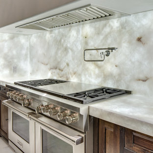 ニューオリンズの巨大なモダンスタイルのおしゃれなキッチン (エプロンフロントシンク、茶色いキャビネット、珪岩カウンター、白いキッチンパネル、石スラブのキッチンパネル、シルバーの調理設備、大理石の床、シェーカースタイル扉のキャビネット、白い床) の写真
