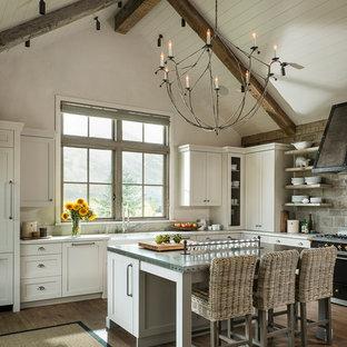 Inredning av ett rustikt l-kök, med en rustik diskho, skåp i shakerstil, vita skåp, svarta vitvaror, mörkt trägolv och en köksö