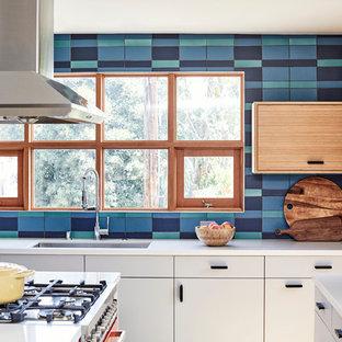 ロサンゼルスの大きいミッドセンチュリースタイルのおしゃれなキッチン (ドロップインシンク、フラットパネル扉のキャビネット、白いキャビネット、マルチカラーのキッチンパネル、セラミックタイルのキッチンパネル、カラー調理設備、淡色無垢フローリング、ベージュの床、白いキッチンカウンター) の写真