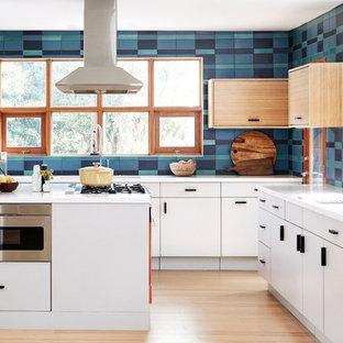 Große Mid-Century Küche in U-Form mit flächenbündigen Schrankfronten, weißen Schränken, bunter Rückwand, Rückwand aus Keramikfliesen, bunten Elektrogeräten, hellem Holzboden, Kücheninsel, beigem Boden, weißer Arbeitsplatte und Unterbauwaschbecken in Los Angeles