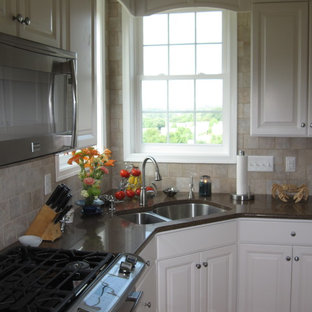Traditional kitchen photos - Example of a classic kitchen design in DC Metro with a double-bowl sink, raised-panel cabinets, white cabinets, laminate countertops, beige backsplash and stone tile backsplash