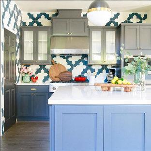 ロサンゼルスのエクレクティックスタイルのおしゃれなキッチン (シェーカースタイル扉のキャビネット、グレーのキャビネット、人工大理石カウンター、マルチカラーのキッチンパネル、セメントタイルのキッチンパネル、シルバーの調理設備、ラミネートの床、グレーの床、白いキッチンカウンター) の写真