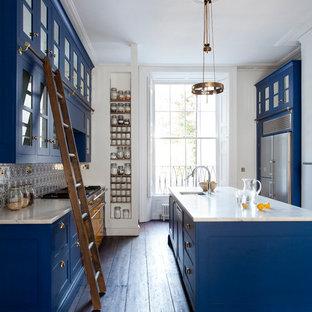 Klassische Küche mit Unterbauwaschbecken, Glasfronten, blauen Schränken, Küchengeräten aus Edelstahl, dunklem Holzboden und Kücheninsel in Dublin