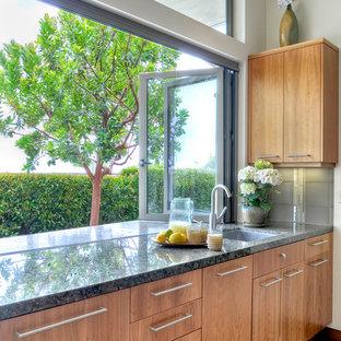 Modern inredning av ett stort kök, med en enkel diskho, släta luckor, skåp i mellenmörkt trä, granitbänkskiva, grått stänkskydd, stänkskydd i glaskakel, integrerade vitvaror och kalkstensgolv